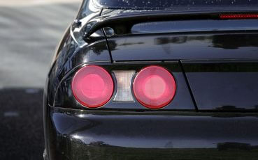 2407094 - car detail - red rear lights of a black sports automobile